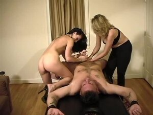 Two dominant babes give a handjob to their slave