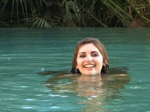 A pretty solo model swims in a pool showing off