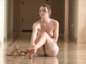 A slim girl with perky tits poses naked sitting on
