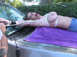 Sara Stone tied and stretched on the hood of car